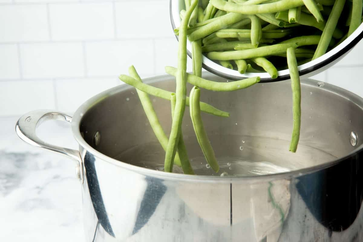 Fresh trimmed green beans in a bowl, tipping into a pot of boiling water.