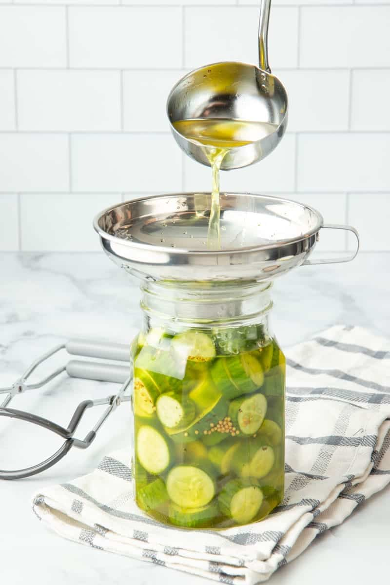 Pouring brine through a wide-mouth canning funnel into a jar of bread and butter pickles.