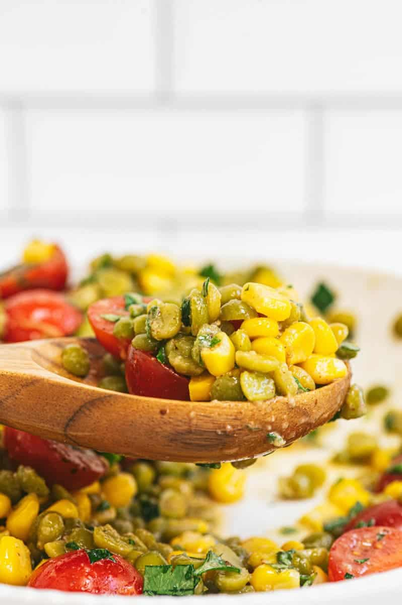 Close-up of wooden spoon with a big scoop of split pea salad over a serving bowl.