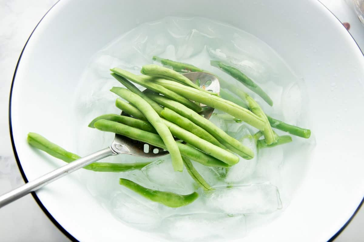 Overhead of a slotted spoon lowering blanched green beans into an ice bath.