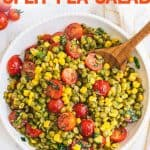 """Overhead of serving bowl full of finished split pea salad with wooden serving spoon scooping up the first serving. A text overlay reads, """"Summer Split Pea Salad."""""""