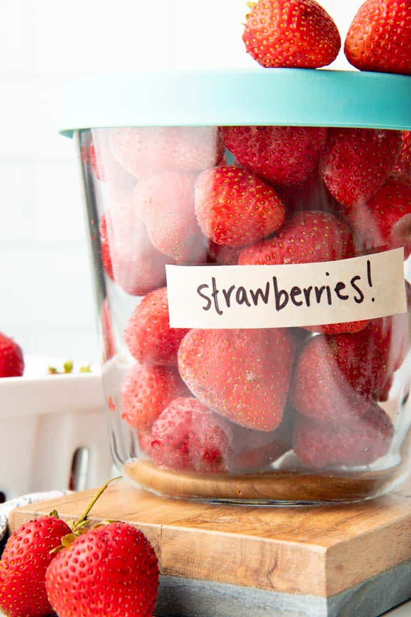Close-up of glass container labeled strawberries filled with individually frozen whole strawberries.