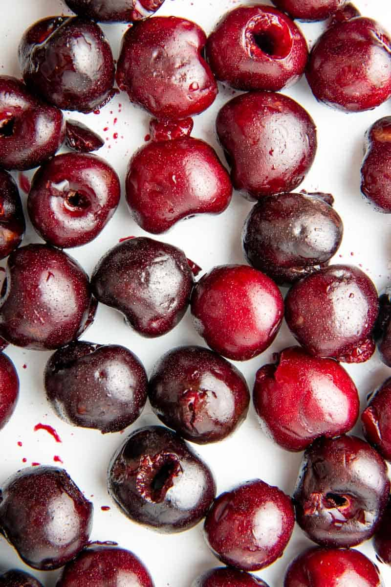 Close-up of fresh, pitted cherries in a single layer on a baking sheet.