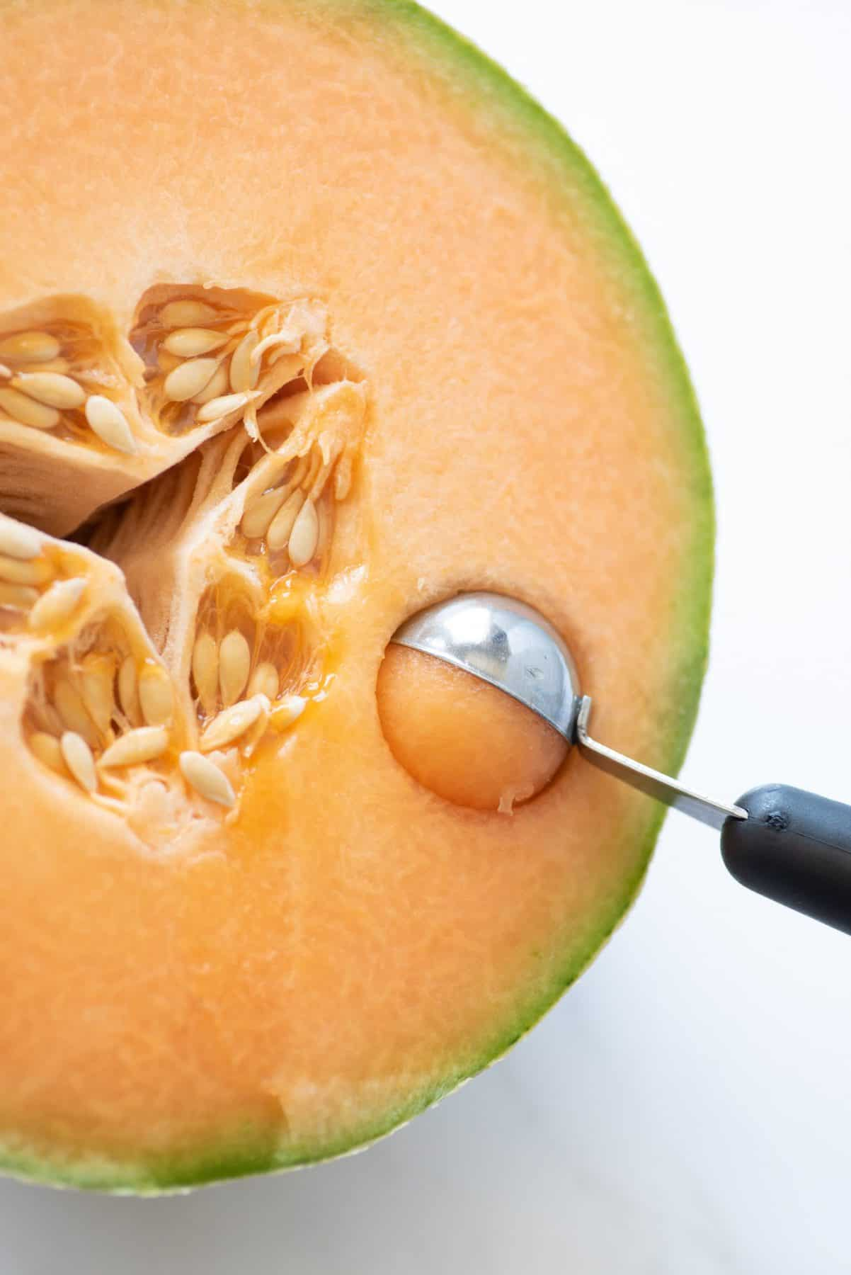 Close-up of melon baller scooping into the cut side of a cantaloupe half.