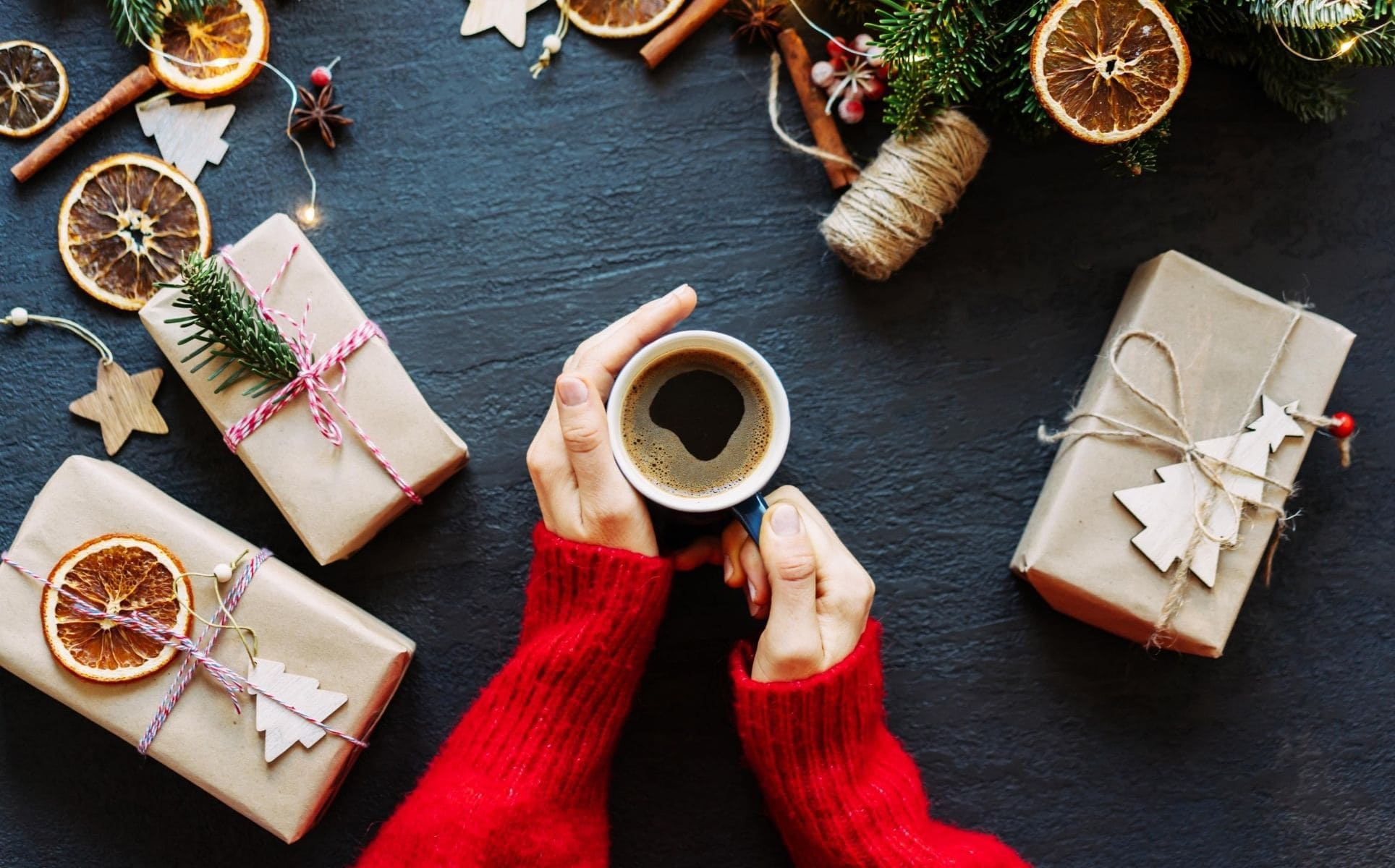 Hand-wrapped gifts surround a pair of hands holding a mug filled with coffee.