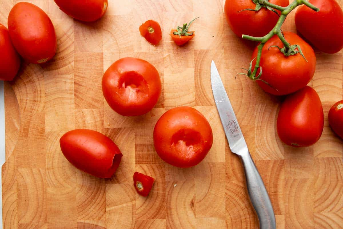 Overhead of three fresh tomatoes in the center of a wooden cutting board with their cores removed.