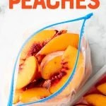 "Overhead of open freezer bag filled with individually frozen peach slices. A text overlay reads, ""How to Freeze Peaches."""