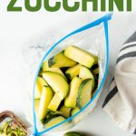 "Overhead of open Hefty freezer bag filled with individually frozen slices of zucchini. A text overlay reads, ""How to Freeze Zucchini."""