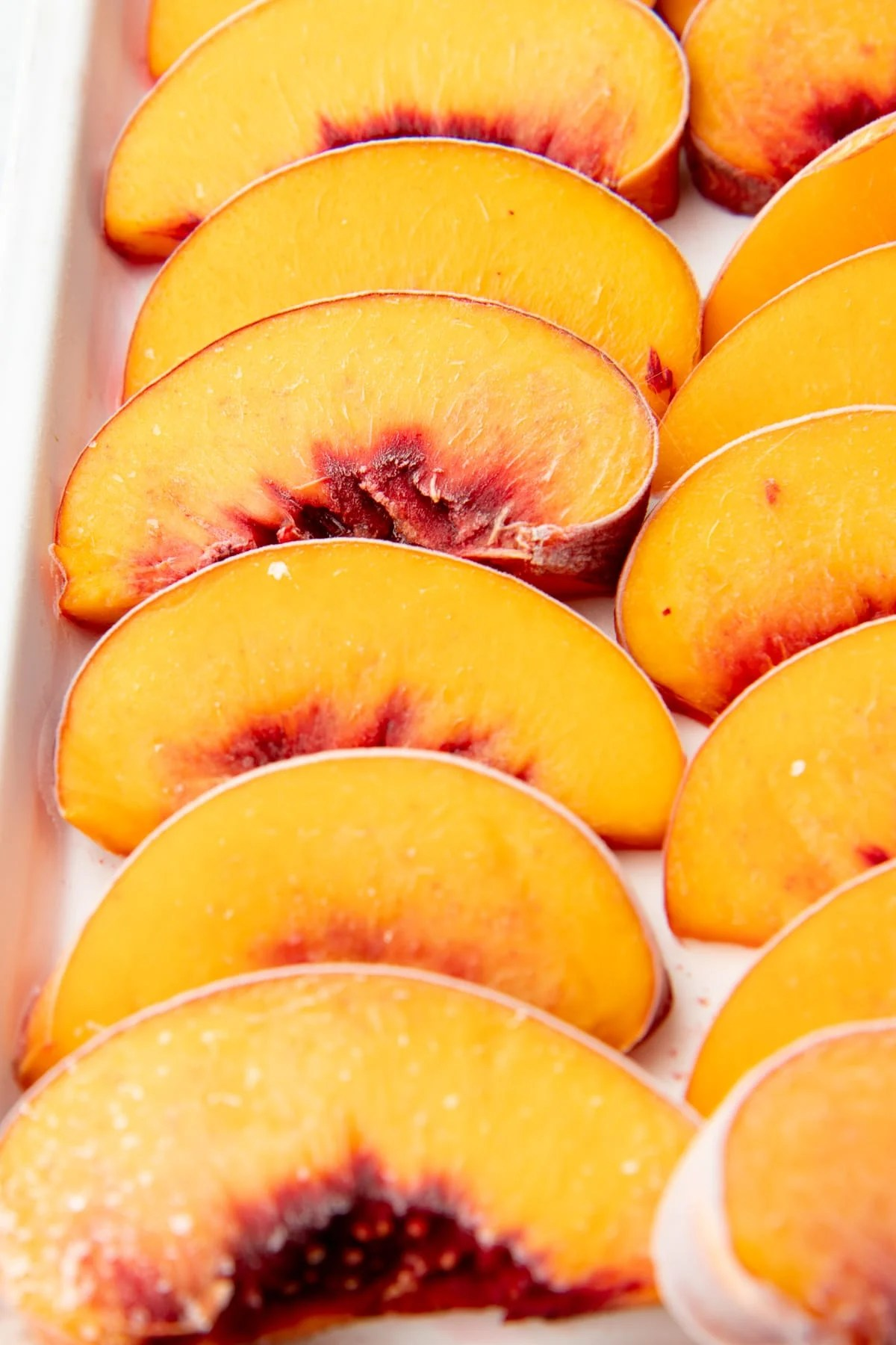 Close-up of individually frozen peach slices on a baking sheet.