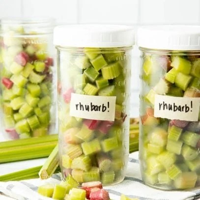 Three jars filled with individually frozen pieces of cut rhubarb standing on a kitchen towel.