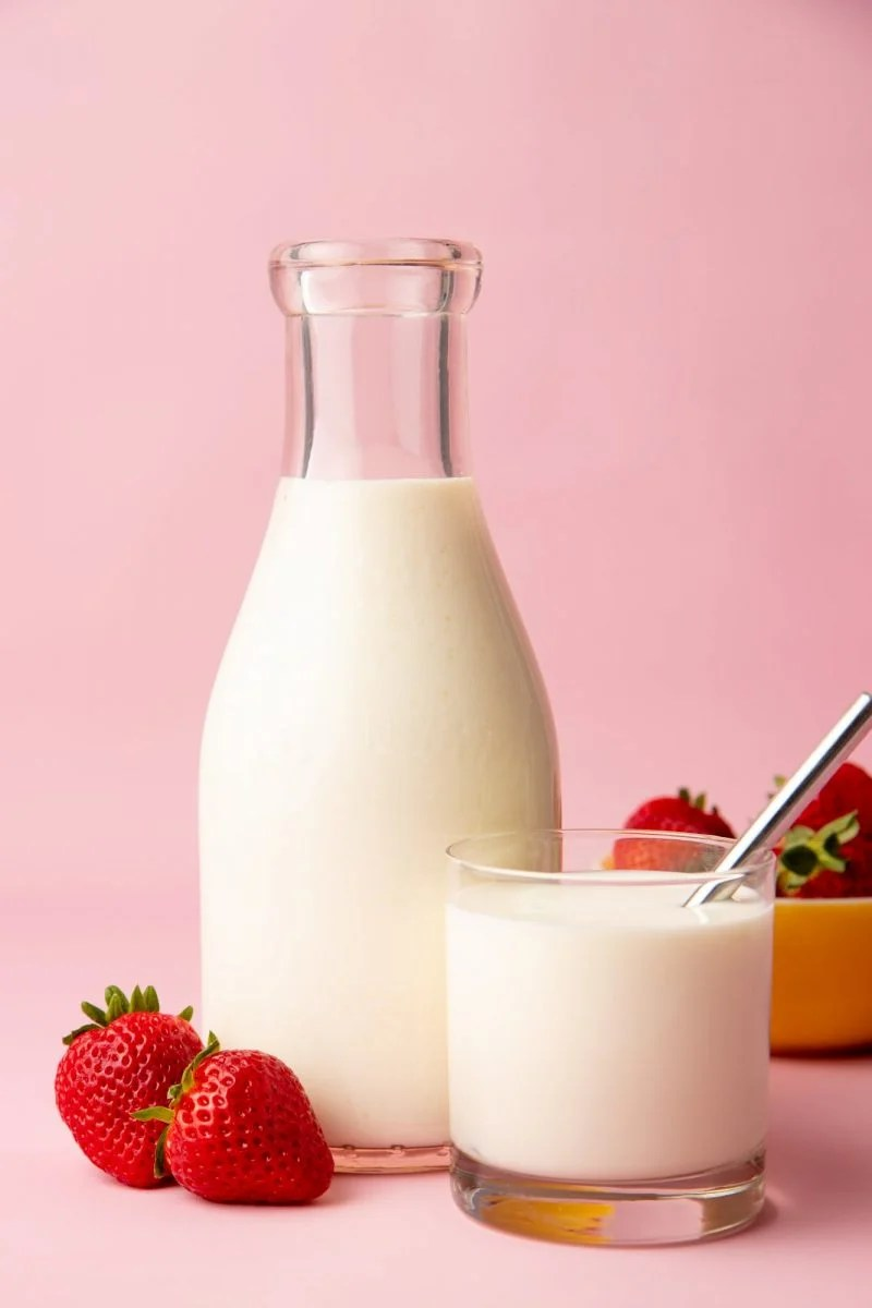 Close-up of a glass carafe and glass tumbler full of homemade kefir with ripe, red strawberries alongside.