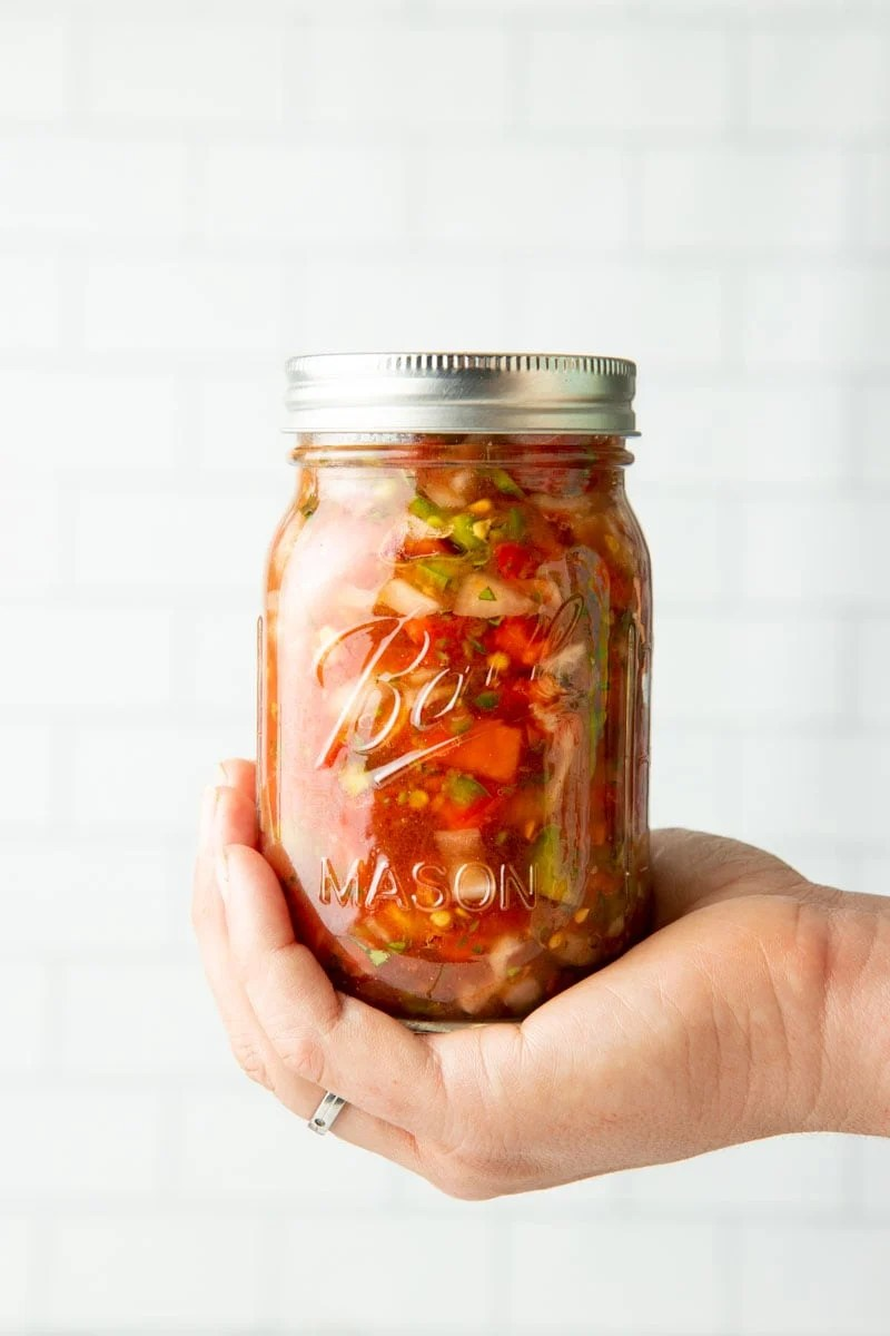 Close-up of a jar of salsa cupped into the palm of someone's hand.