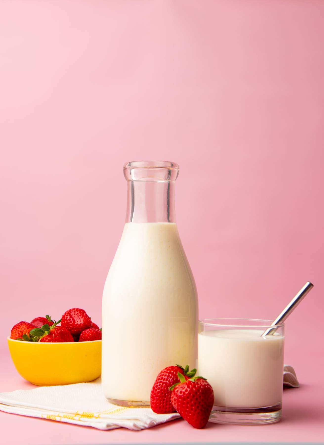 A glass carafe filled with homemade kefir sits on a linen kitchen towel with a full tumbler and a bowl of fresh strawberries on either side of it.