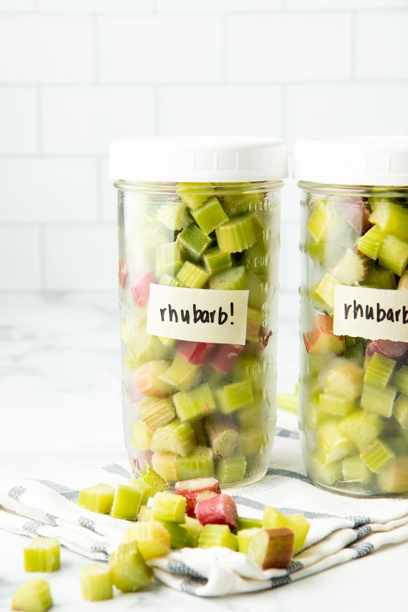 Close-up of two mason jars labeled and filled with individually frozen pieces of cut rhubarb, standing up on a kitchen towel.