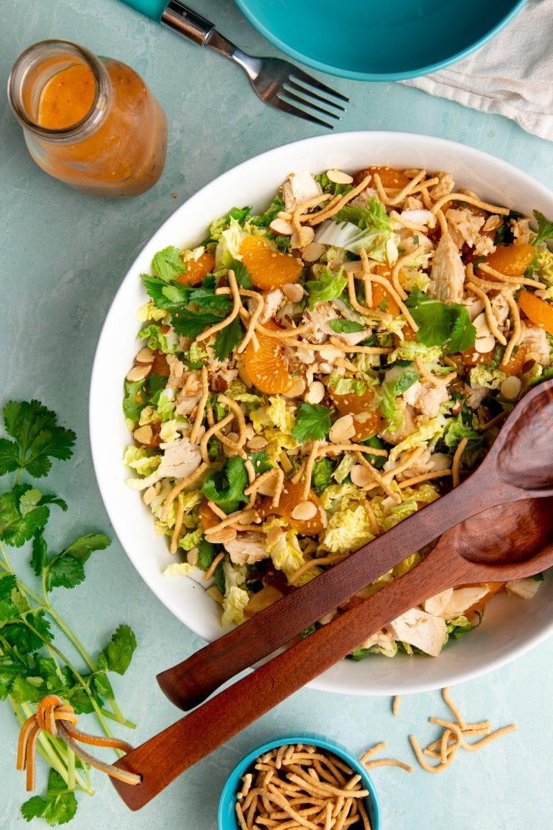 Overhead of large serving bowl of finished chicken salad and arranged around it are the homemade dressing, fresh cilantro, and crunchy chow mein noodles to garnish.