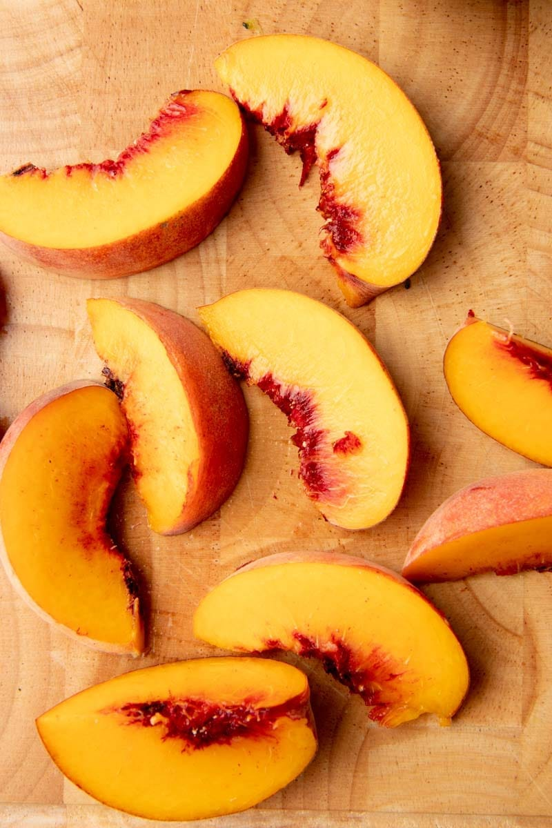 Close-up of fresh peach slices on a wooden cutting board.