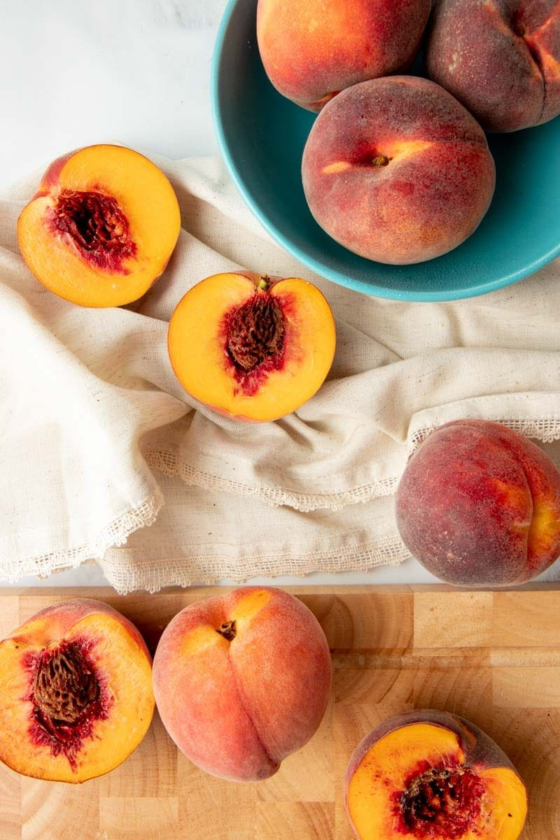 Overhead of whole and halved fresh peaches on kitchen linen and a wooden cutting board.