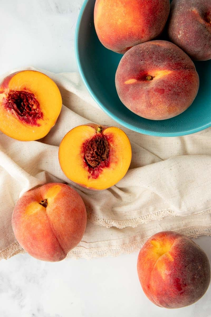 Overhead of whole, fresh peaches in a bowl and halved peaches on kitchen linen.