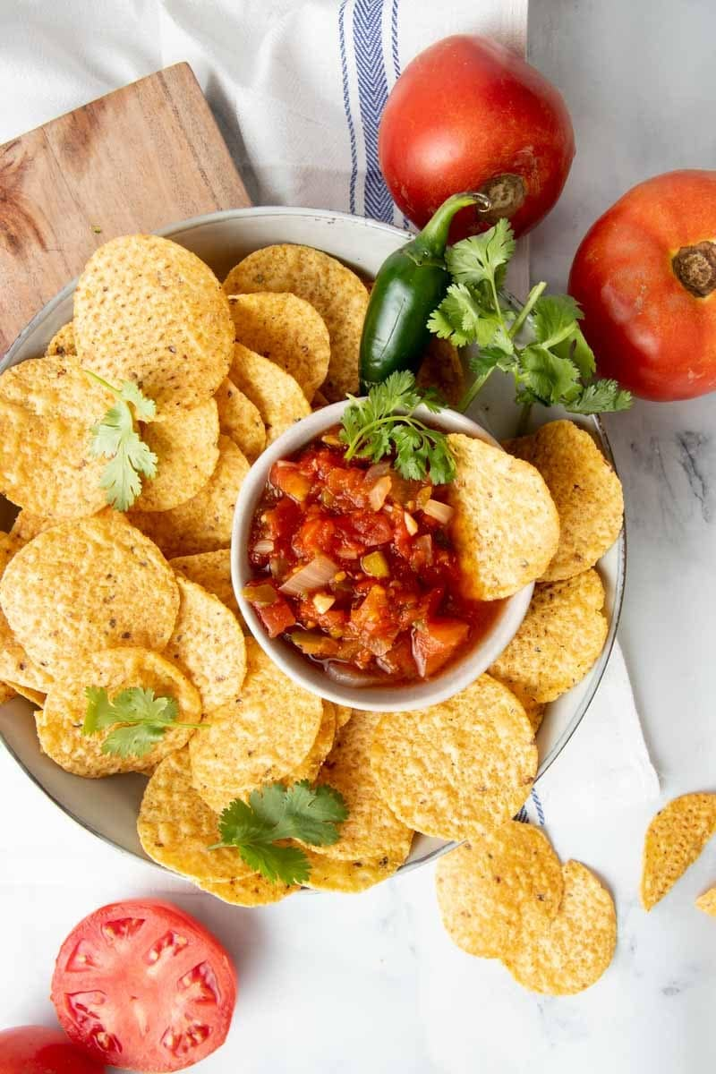 Overhead of a platter of tortilla chips with a bowl of zesty salsa nestled among the chips.