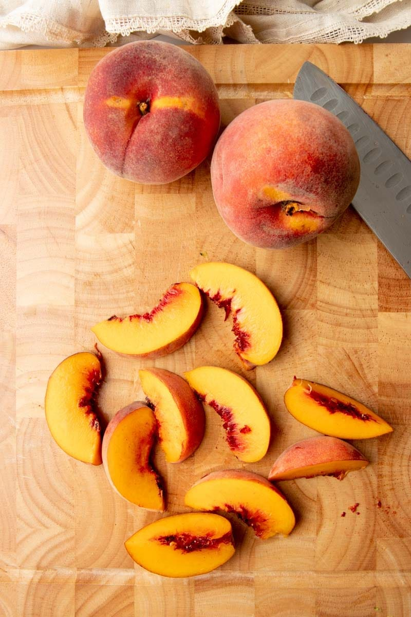 Overhead of fresh peach slices on a wooden cutting board with two whole peaches and a knife.