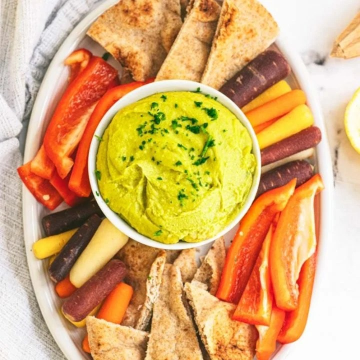 Overhead of a party platter with a bowl of split pea hummus in the center surrounded by pita chips, rainbow carrot sticks, and red bell pepper strips.