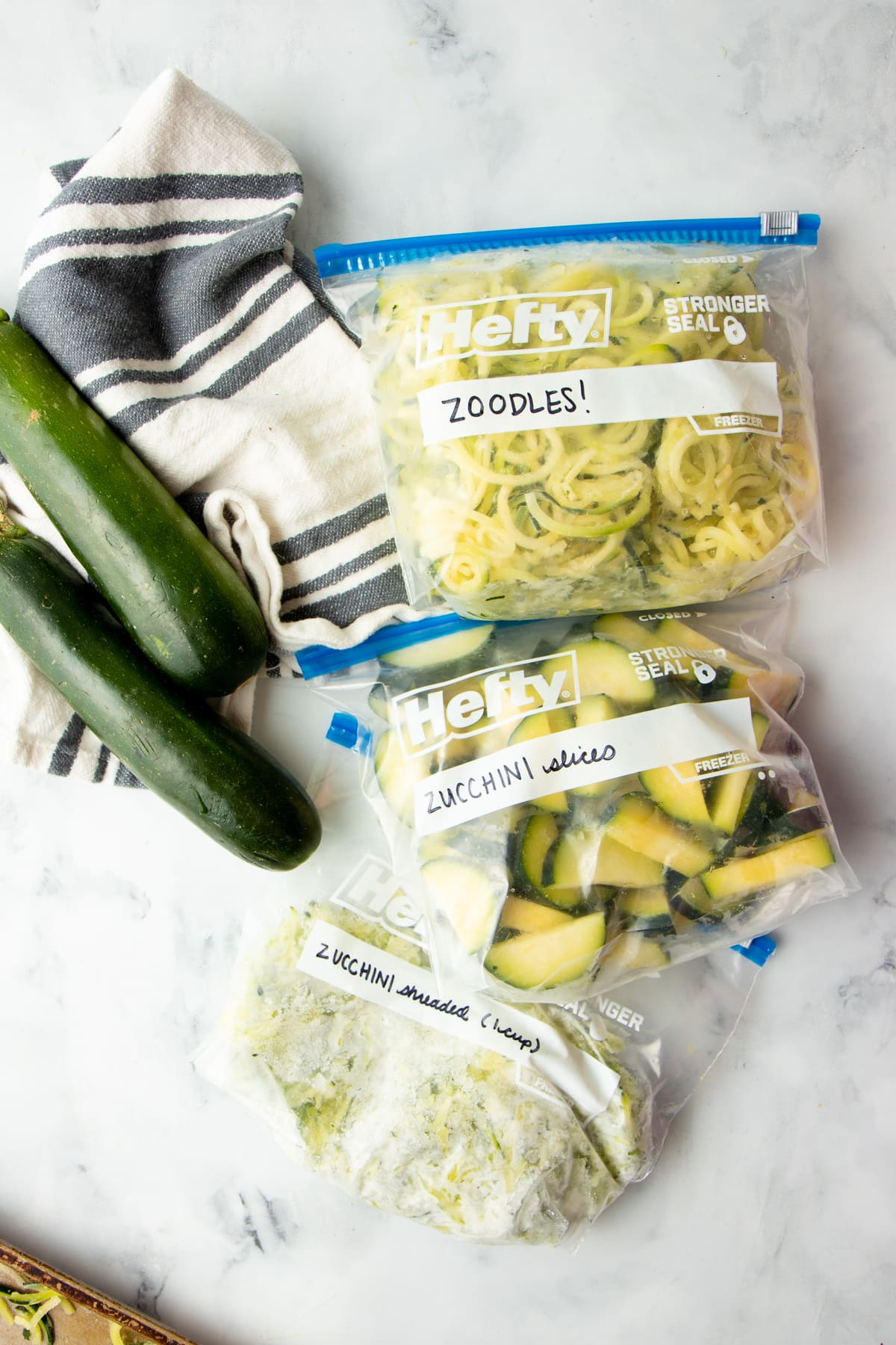 Three Hefty freezer bags filled with frozen sliced zucchini, frozen zucchini noodles, and frozen shredded zucchini.