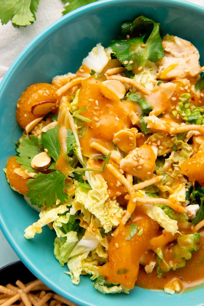 Close-up of a single serving of mandarin chicken salad in a bowl with dressing on top.