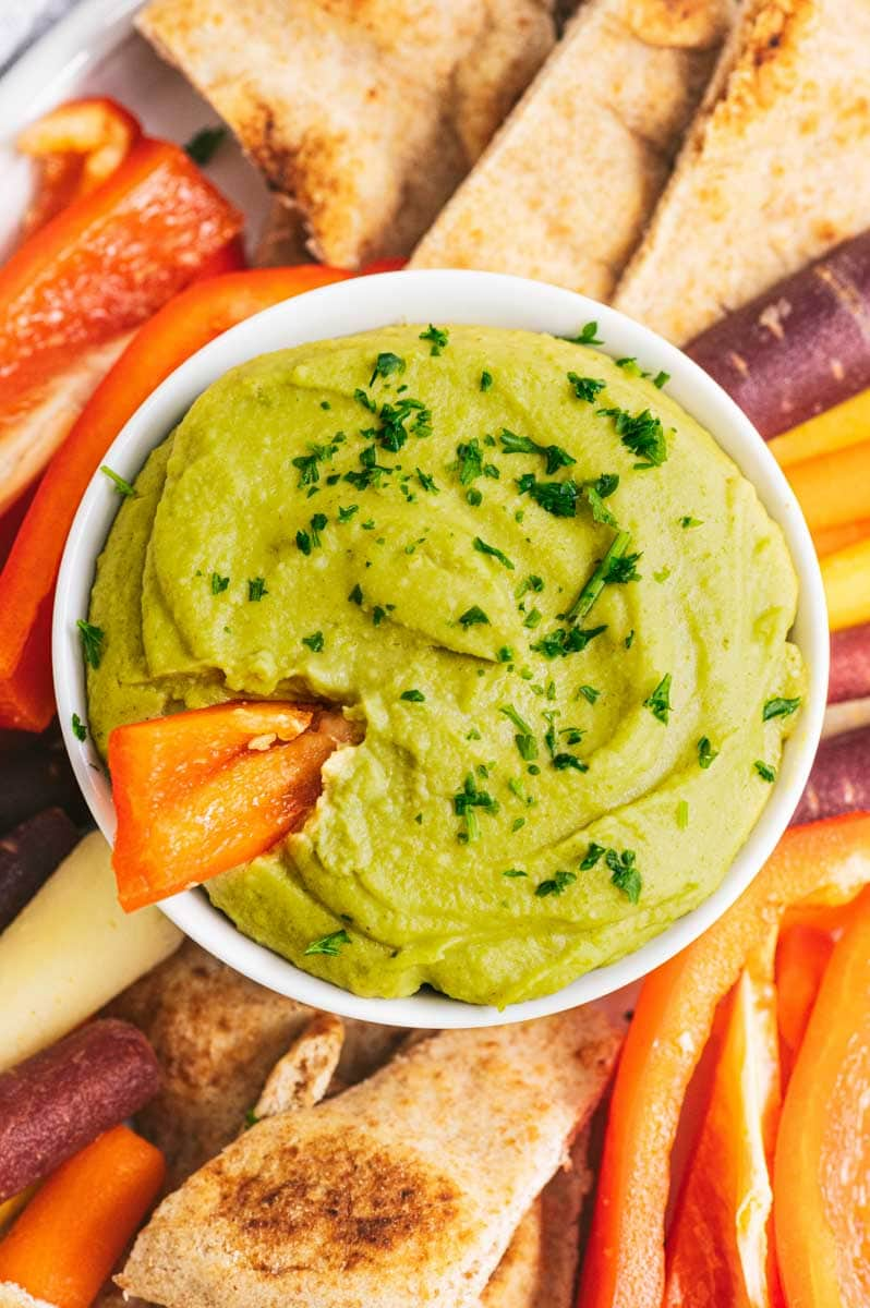 Close-up of a bowl of finished split pea hummus with a red bell pepper strip dipped into it.