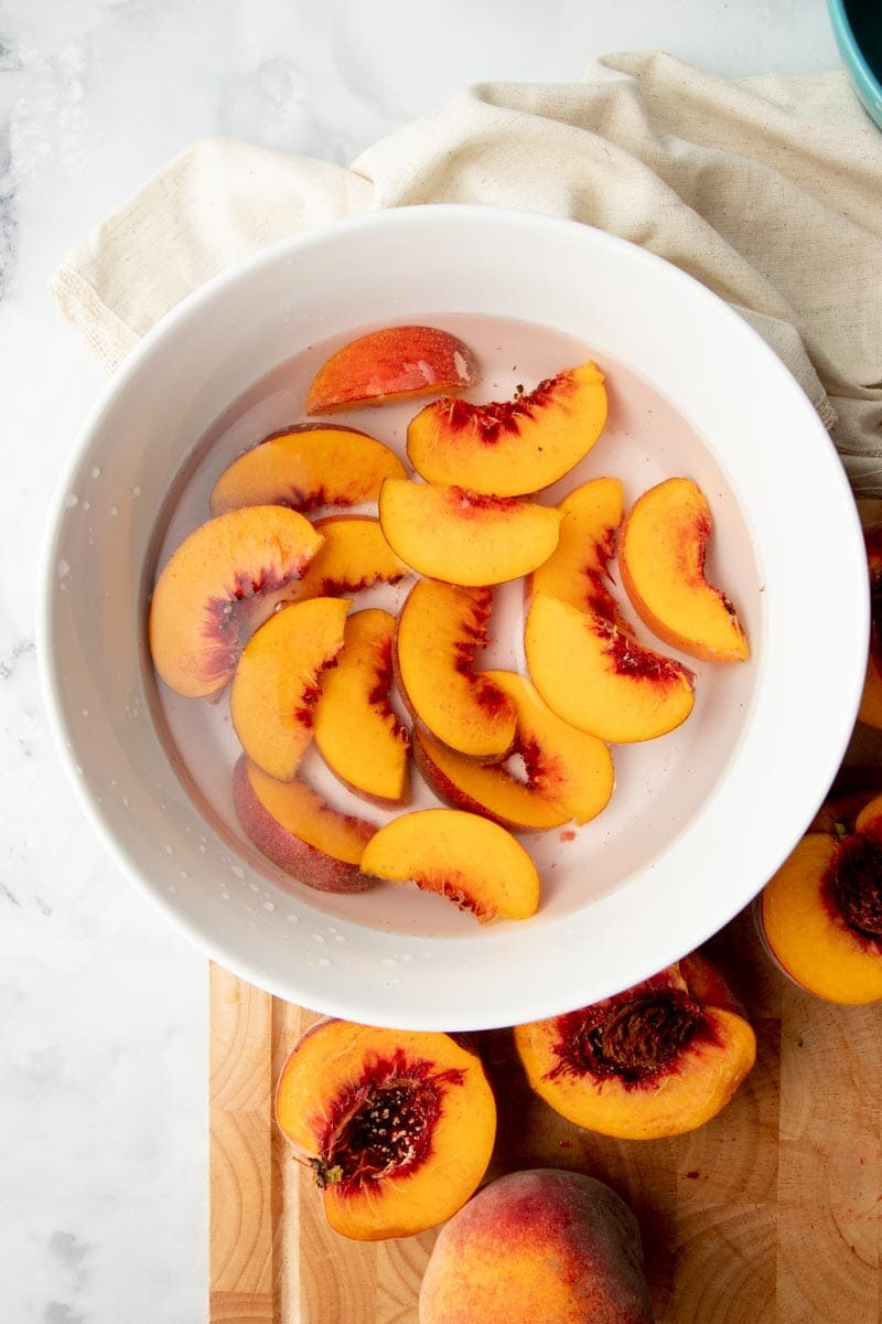 Overhead of fresh peach slices in a bowl filled with water and lemon juice to prevent browning.