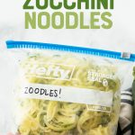 "Close-up of a hand holding a Hefty freezer bag labeled ""Zoodles!"" filled with frozen zucchini noodles. A text overlay reads, ""How to Freeze Zucchini Noodles."""