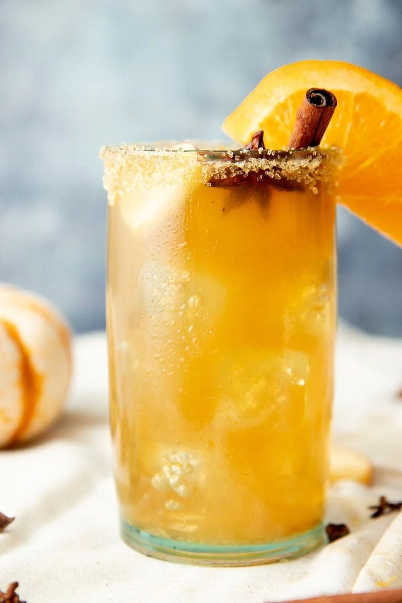 Chilled glass of spiked cider filled with ice and garnished with sugar rim, cinnamon stick, star anise pod, and orange slice.