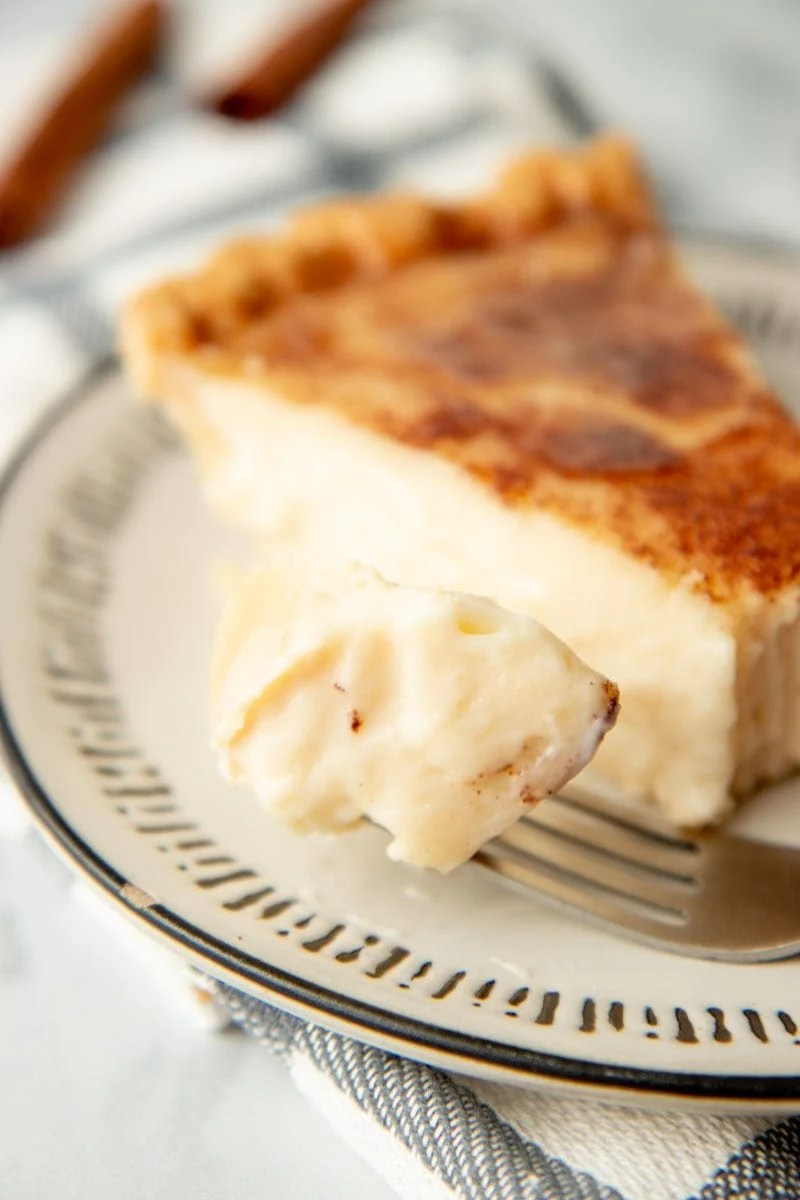 Close-up of a bite of sugar cream pie on a fork.