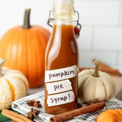 A full bottle of pumpkin spice syrup with pumpkins and whole spices around it.