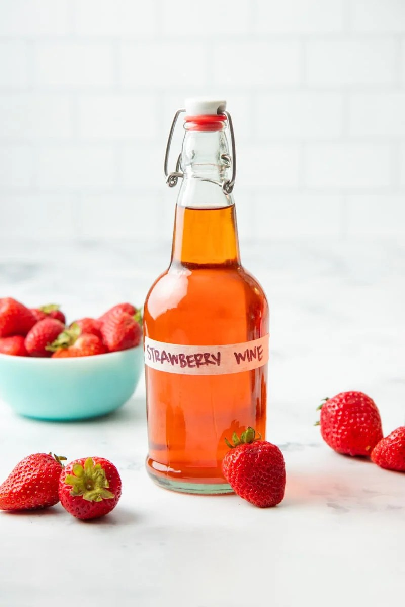 A glass flip-top bottle of homemade strawberry wine sits with fresh strawberries around it.