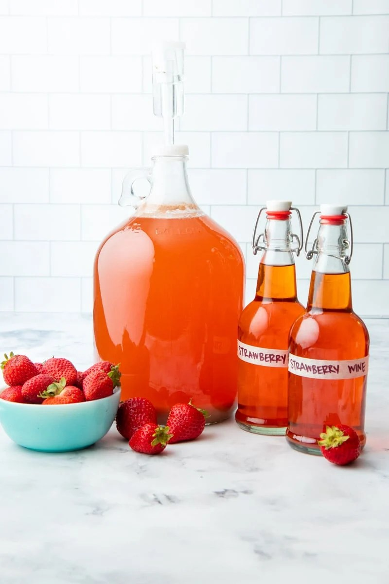 A carboy of strawberry wine with a 3-piece airlock sits beside two flip-top bottles filled with finished fruit wine.