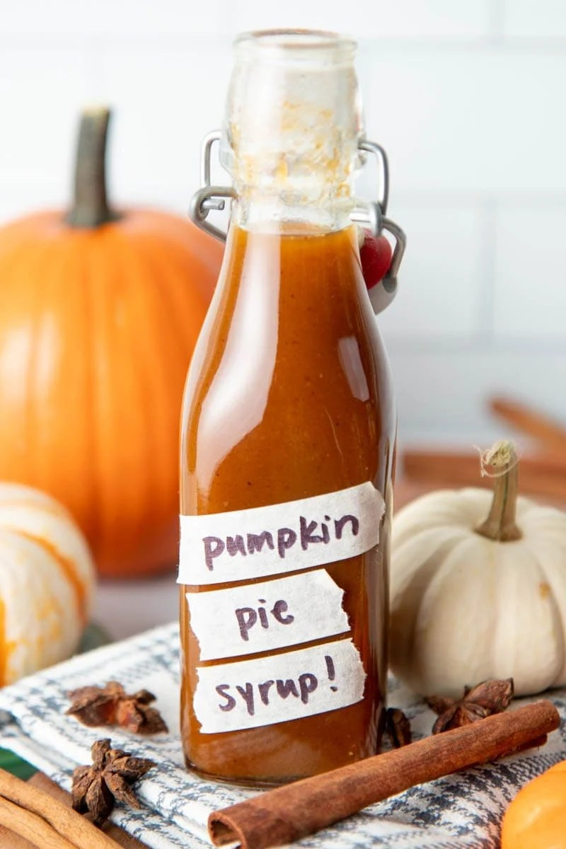 Close-up of a glass, flip-top bottle of pumpkin spice syrup labeled with masking tape.