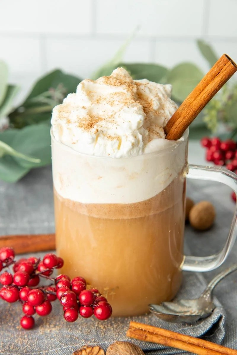 Close-up of a full mug of hot buttered rum with whipped cream, nutmeg, and cinnamon stick garnish.