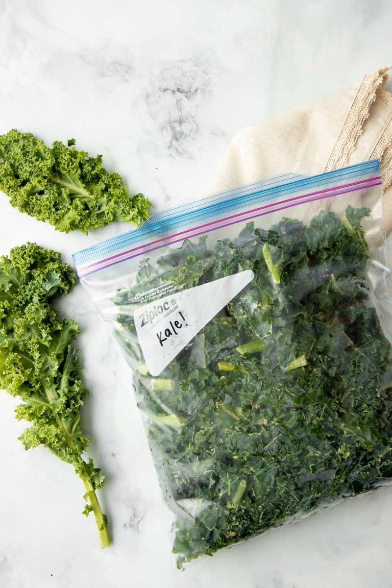 Frozen kale in a closed, zip-top bag with fresh kale beside it.