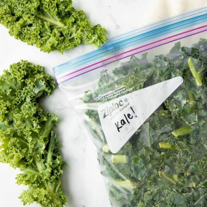 Close-up of frozen kale in a Ziploc freezer bag.