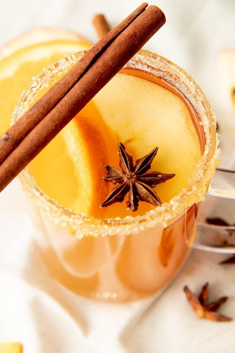 The top of a mug of spiked apple cider showing the sugar rim, cinnamon stick, and star anise garnishes close up.