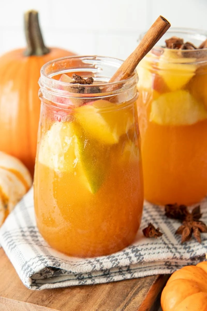 Glass jar filled with autumn sangria and apples chunks.