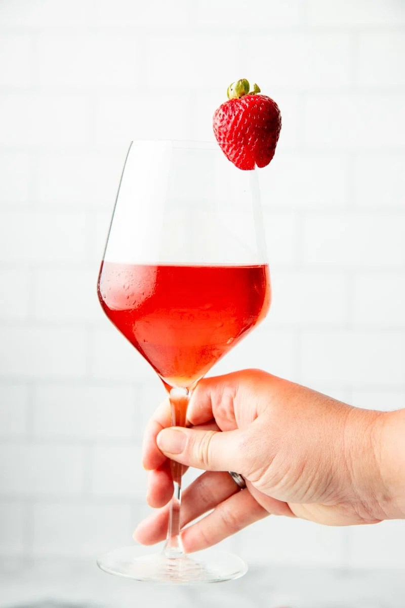 Close-up of hand holding a glass of strawberry wine.