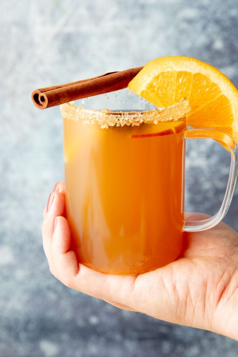 Close-up of hand cupping the bottom of a mug of hot apple cider garnished with a sugar rim, orange slice, and cinnamon stick.