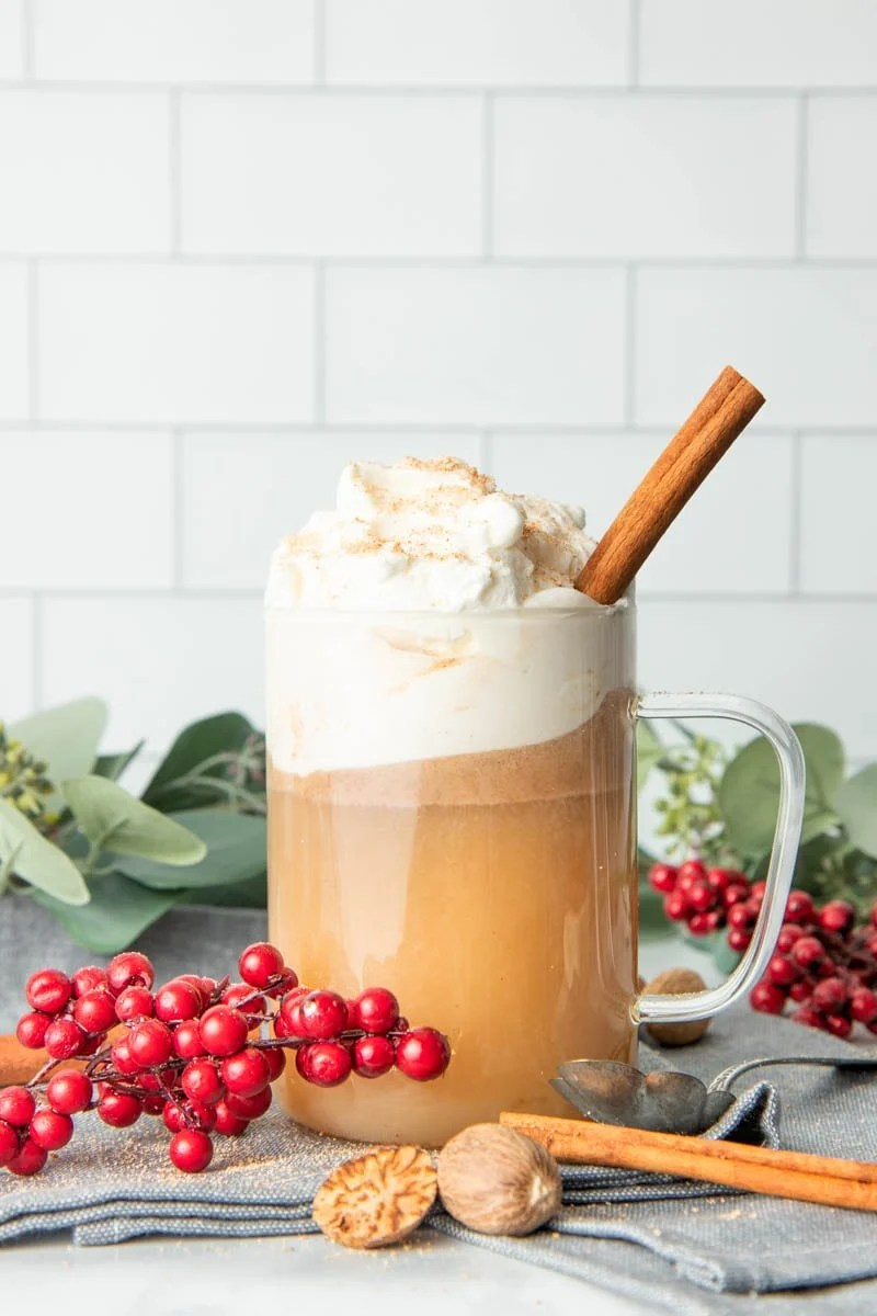 A glass mug filled with hot buttered rum, topped with whipped cream, and garnished with nutmeg and a cinnamon stick.