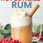 "A glass mug filled with hot buttered rum, topped with whipped cream, and garnished with nutmeg and a cinnamon stick. A text overlay reads, ""Single Drink or For a Crowd! Hot Buttered Rum."""