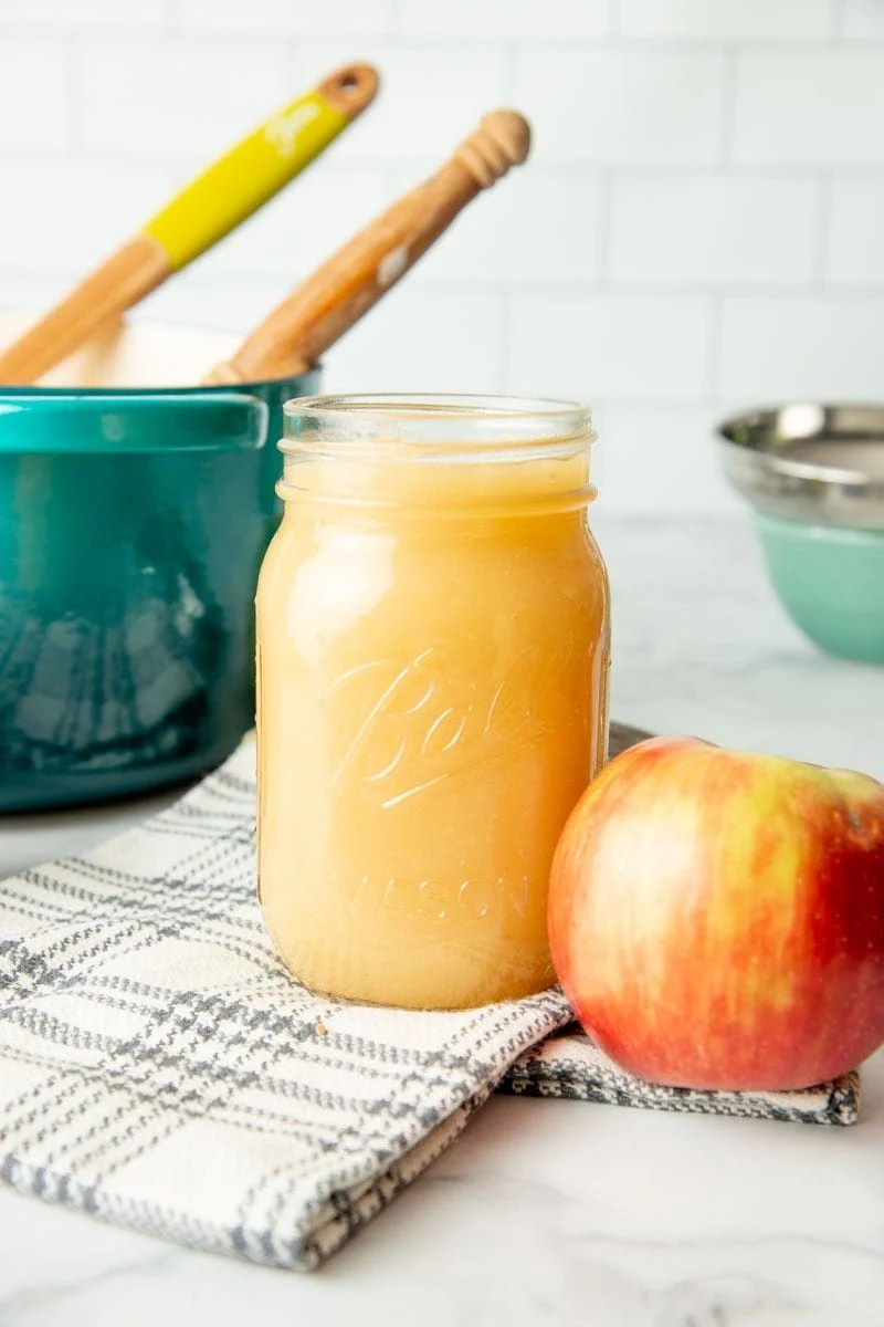 A full pint jar of applesauce for canning sits next to a fresh apple.