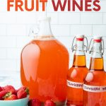 "A carboy of strawberry wine with a 3-piece airlock sits beside two flip-top bottles filled with finished fruit wine. A text overlay reads, ""How to Make Fruit Wines."""