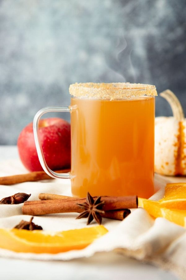 A mug of apple cider spiked with bourbon sits with steam rising from the top surrounded by orange slices, whole spices, an apple and a pumpkin.