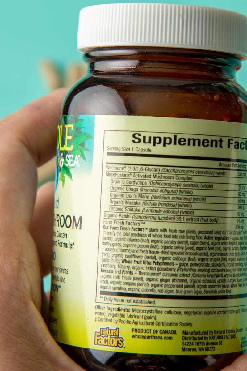 Close-up of a hand holding a bottle of herbal supplements to show the label on the back listing its organic ingredients.