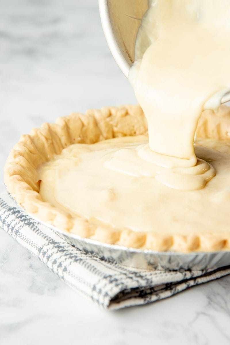 Close-up of pouring sugar pie filling into crust.